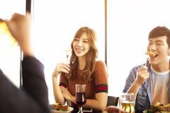 молодые друзья наслаждаются обедающим в ресторане стоковые изображения rf