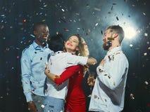 Молодые друзья обнимая на партии Eve Новых Годов стоковое фото rf