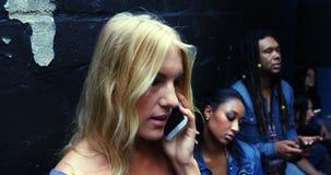 Молодые друзья отправляя СМС и говоря на телефоне, 4K 4k акции видеоматериалы