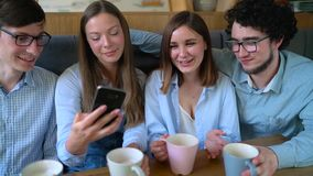 Молодые друзья сидят в кафе, выпивают кофе и имеют потеху связывая движение медленное видеоматериал