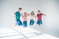 Молодые друзья скача совместно Стоковое Изображение