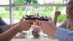 Молодые друзья clink стекла красного вина и выпивать на ресторане сток-видео