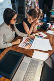 Молодые женские график-дизайнеры сидя на столе при компьтер-книжка, диаграммы цвета и некоторые эскизы обсуждая новый проект Стоковое Изображение