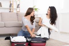 Молодые женские друзья пакуя одежды в сумку перемещения стоковое изображение