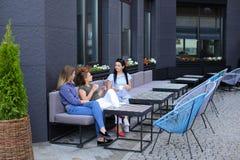 Молодые женские люди отдыхая на кафе и выпивая coffe около зеленого растения Стоковые Фотографии RF