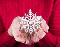 Молодые женские руки держа белую снежинку на предпосылке красного цвета Стоковая Фотография RF