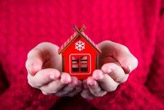 Молодые женские руки держа меньший деревянный дом зимы на красном bac Стоковая Фотография RF