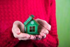 Молодые женские руки держа меньший деревянный дом зимы на красном bac Стоковые Изображения