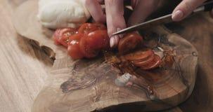 Молодые женские руки отрезая томат вишни на деревянной доске Стоковые Изображения