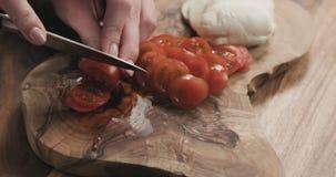 Молодые женские руки отрезая томат вишни на деревянной доске Стоковое фото RF