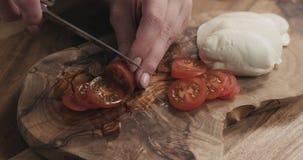 Молодые женские руки отрезая томат вишни на деревянной доске Стоковое Изображение RF