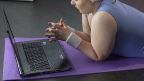 Молодые женские смотря ногти, после этого сердито на надоеданном экране компьютера, сток-видео