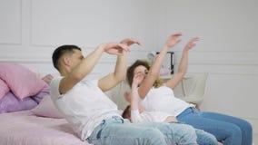 Молодые женщина и мальчик семьянина падают на кровать, замедленное движение сток-видео