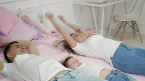 Молодые женщина и мальчик семьянина падают на кровать, замедленное движение видеоматериал
