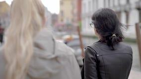 Молодые женщины блондинкы и брюнета идут совместно в город в дневном времени вдоль обваловки реки, заднего взгляда сток-видео