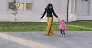 Молодые женщины брюнет стильные идя с маленьким ребёнком в городском парке видеоматериал