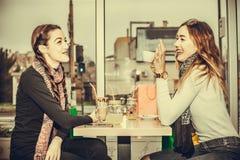 Молодые женщины выпивая кофе и говорить Стоковые Изображения RF
