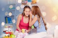 Молодые женщины выпивая чай и злословя дома Стоковое фото RF