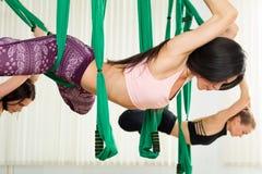 Молодые женщины выполняя антигравитационную тренировку йоги Стоковые Фото