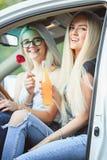 Молодые женщины в автомобиле усмехаясь и выпивая сок Стоковые Изображения RF