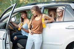 Молодые женщины в автомобиле усмехаясь и выпивая сок Стоковые Фотографии RF
