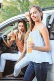 Молодые женщины в автомобиле усмехаясь и выпивая сок Стоковое Изображение