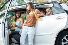 Молодые женщины в автомобиле усмехаясь и выпивая сок Стоковые Фото