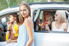 Молодые женщины в автомобиле усмехаясь и выпивая сок Стоковая Фотография RF