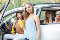 Молодые женщины в автомобиле усмехаясь и выпивая сок Стоковые Изображения