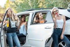Молодые женщины в автомобиле усмехаясь и выпивая сок Стоковое Изображение RF