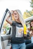 Молодые женщины в автомобиле усмехаясь и выпивая сок Стоковое фото RF