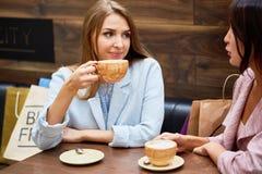 Молодые женщины в кафе на торговом центре Стоковые Изображения