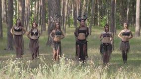 Молодые женщины в красивых костюмах дриад или нимфах леса показывая представление в заколдованном лесе или делая ритуал видеоматериал