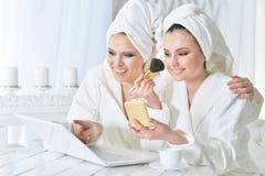Молодые женщины в купальных халатах с компьтер-книжкой Стоковые Фото
