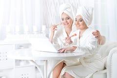 Молодые женщины в купальных халатах с компьтер-книжкой Стоковое Изображение