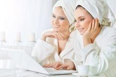 Молодые женщины в купальных халатах с компьтер-книжкой Стоковая Фотография RF