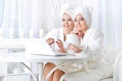 Молодые женщины в купальных халатах с компьтер-книжкой Стоковые Изображения