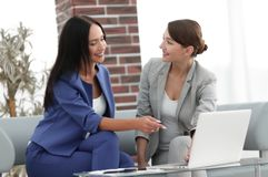 Молодые женщины в офисе работая совместно на настольном компьютере Стоковые Изображения