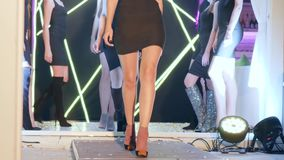 Молодые женщины в платья коктеиля и в ботинках замши теплых на пятках идут в строку по-одному через подиум сток-видео