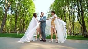 Молодые женщины в сексуальных bridal костюмах танцуют вокруг человека стоя все еще в парке видеоматериал