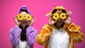 Молодые женщины в смешных пижамах закрывая глаза с donuts, околпачивая вокруг, шутка стоковые изображения rf
