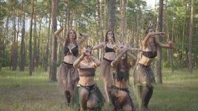 Молодые женщины в театральных костюмах жильцов или дьяволов леса танцуя в представлении показа леса или делая ритуал сток-видео
