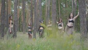Молодые женщины в театральных костюмах жильцов или дьяволов леса показывая представление в заколдованном лесе или делая ритуал акции видеоматериалы