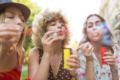 Молодые женщины дуя пузыри мыла outdoors стоковое фото rf