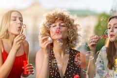 Молодые женщины дуя пузыри мыла outdoors стоковое фото
