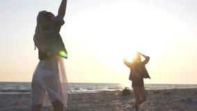 Молодые женщины замедленного движения одетые в куртках джинсовой ткани имея потеху на seashore в вечере в лучах захода солнца сток-видео