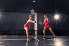 Молодые женщины играя бадминтон на спортзале Стоковая Фотография