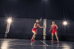 Молодые женщины играя бадминтон на спортзале Стоковое Изображение