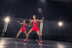 Молодые женщины играя бадминтон на спортзале Стоковое Изображение RF