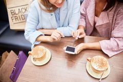 Молодые женщины используя Smartphone на таблице в кофейне Стоковые Изображения